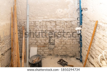 Construction site of a bathroom under construction with wooden slats, spirit level, bucket and dustpan with copy space Photo stock ©