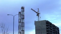 construction site of a new apartment building in the evening with a construction crane finished work and towers from metal structures, a new house under construction and construction equipment