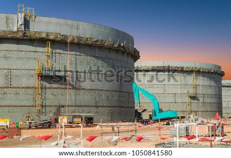 Construction site of oil and gas industrial, Huge oil storage tank ,Heavy construction machine doing building  with the workers  stock photo