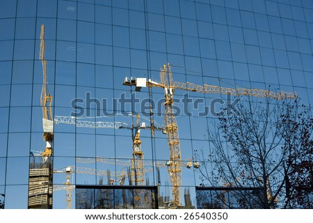 Construction site reflected in a glass facade building