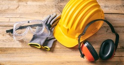 Construction site safety. Protective hard hat, headphones, gloves and glasses on wooden background