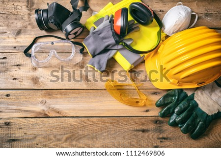 Construction site safety. Protective hard hat, headphones, gloves, glasses and masks on wooden background, copy space, top view