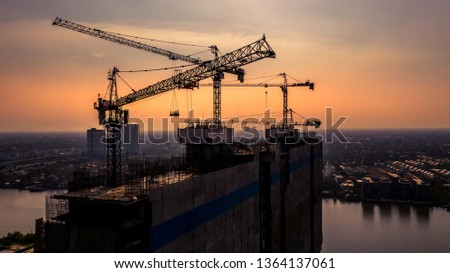 Construction site silhouette background, Hoisting cranes and new multi-storey buildings, Aerial view Industrial building construction architecture background.