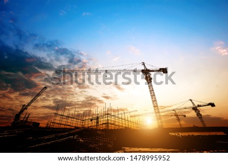 Construction site, silhouettes of construction industry workers on scaffolding against the sunset light. #1478995952