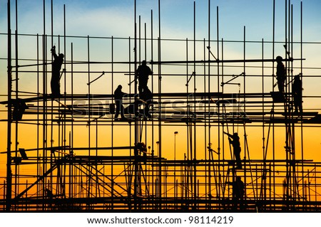 Construction site, silhouettes of construction industry workers on scaffolding against the sunset light.