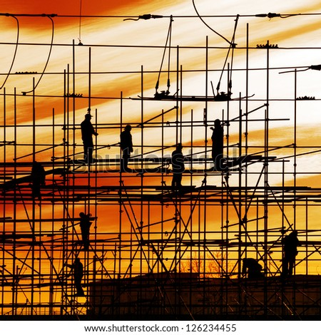 Construction site, silhouettes of workers on scaffolding against the light