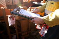 Construction site supervisor inspecting checking names list at safe task isolation procedure permit holder box to ensure all construction miners are locking on correct permit prior to work on site
