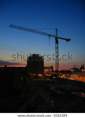 Construction site with a crane against a sky at sunset