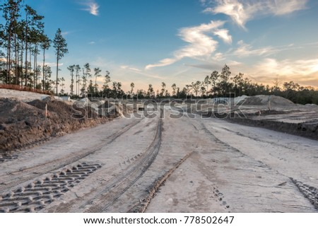construction site with construction materials, vehicles and earth movers