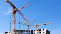 Construction site with crane on blue sky background. Civil engineering. Building of new multi-story apartment house. Real estate investing. Housing development. Buy, sale, rental and insurance flat.