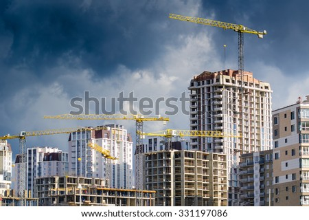 Construction site with cranes and unfinished buildings under the stormy sky.