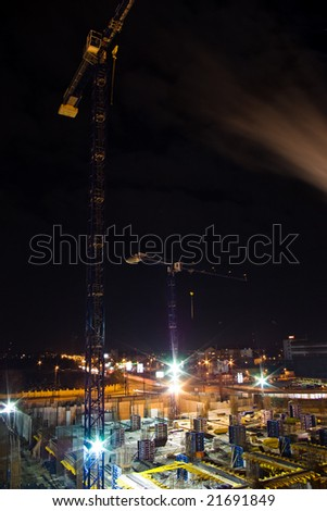 construction site with cranes at night