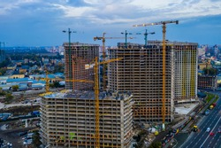 Construction site with cranes at sunset. Construction of an apartment building