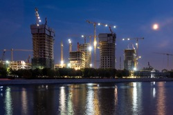 Construction site with cranes for high rise buildings at river. Night blue sky with half moon. City life style.