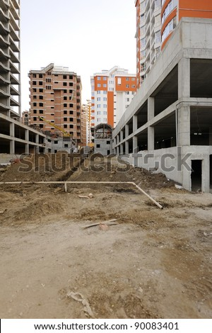Construction site with great perspective showing finished houses in the background. Useful file for your construction site, brochure or advertising about your new apartment complex.