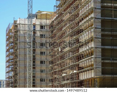 Construction site with new modern high-rise apartment buildings exteriors in scaffolding