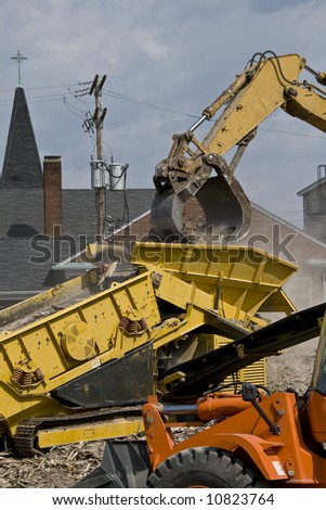 Construction site with rubble being put into a dump truck with a bulldozer in the foreground