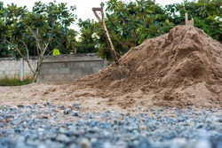 construction site with shovels on pile of rock and sand