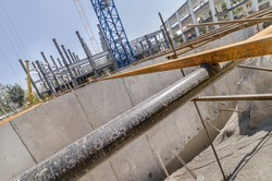Construction site with surrounding wall or tilt-up panels and girders Deep foundations made of huge cement slabs