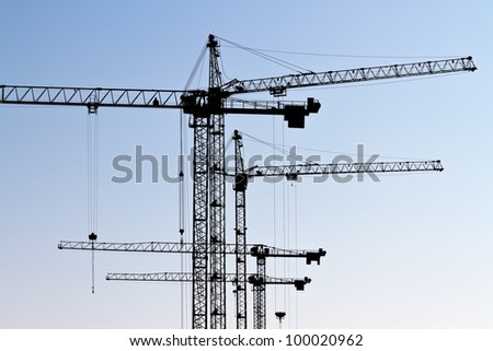 Construction site with tower cranes silhouettes