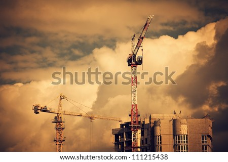 Construction site with two cranes and clouds on background. Industrial urban landscape