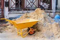 construction site with wheel barrow with sand