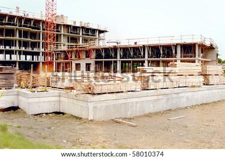 construction site work in progress . lumber and foundation concrete in the foreground with crane and incompleted multi storey levels in the background
