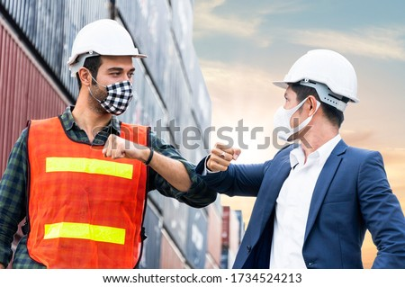 construction site worker and foreman wearing hygiene face mask elbow bump greeting in New Normal adaptation to prevent Coronavirus or Covid-19 spreading. social distance working style at warehouse