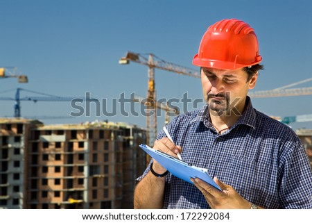 Construction site worker looking at paper,controls quality of the construction