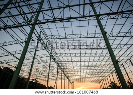 Construction Steel Frame Building Construction of steel frame building warehouse structure bolt nut secured welded  together piece by piece until fully complete enclosed structure.