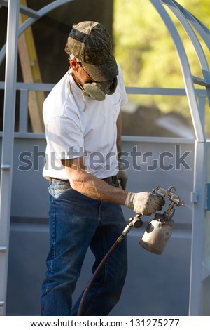 Construction steel worker uses a paint sprayer to apply a primer coat to metalwork.