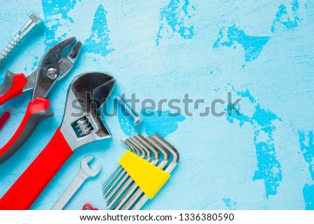 Construction tooling on the blue stone background. Hammers, screws, saw, yellow tape and other small repair tools. Top view. Close up.