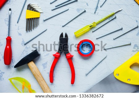Construction tooling on the stone background. Hammers, screws, saw, yellow tape and other small repair tools. Top view. Close up.