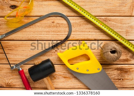 Construction tooling on the wooden background. Hammers, saw, yellow tape and other small repair tools. Top view. Close up.