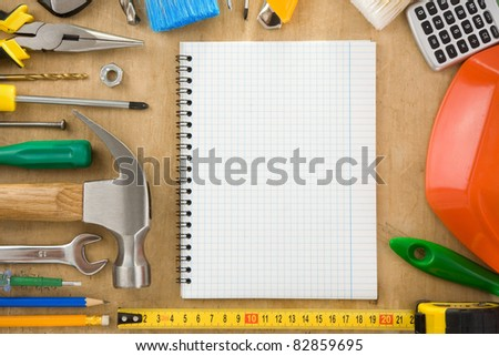 construction tools and notebook on wood texture