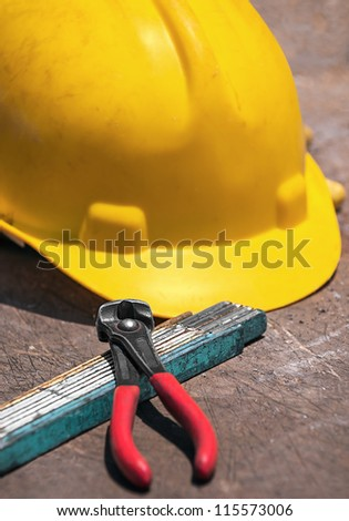 Construction tools - protective helmet, folded ruler, nippers for binding wires -  on construction workshop table
