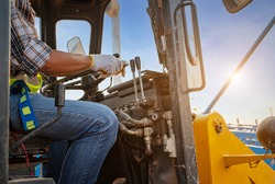 Construction truck driver worker in blue jeans,fashion plaid shirt wearing artificial safety helmet and safety belt working in construction size