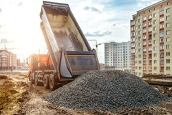Construction truck tipping dumping gravel on road construction site,tip truck and ripper at work preparing ground for new housing estate,Dump truck unloading process,