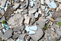 Construction waste, broken concrete panels, tiles on ground in sunny day, top view.