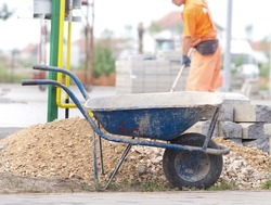 Construction wheelbarrow standing beside gravel and concrete curb stones at building site. Worker in background