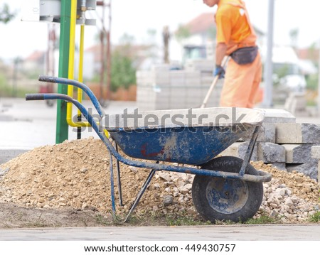 Construction wheelbarrow standing beside gravel and concrete curb stones at building site. Worker in background #449430757