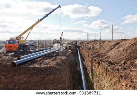 Construction work on the pipe laying of the pipeline into the trench using a crane