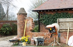 Construction work with tools and cement mixer, building a brick garden wall outside a UK house