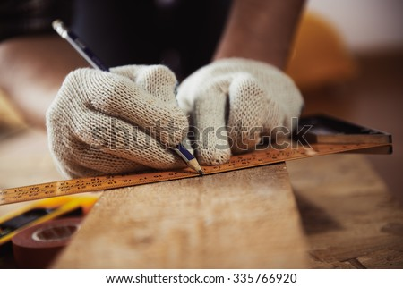 Construction work. Woodwork. Male builder marking point on plank sitting on the floor.