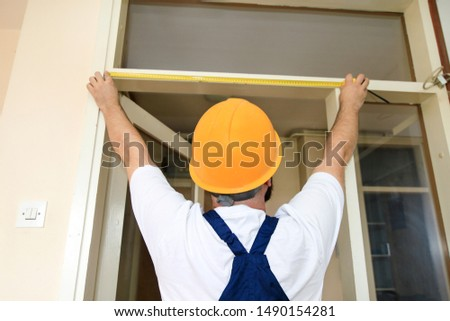 Construction worker and handyman is working on renovation of apartment. Builder is measuring of room door using measure tape at construction site. Renovation concept. Construction and service tools.