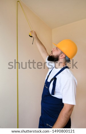 Construction worker and handyman is working on renovation of apartment. Builder is measuring wall of room using measure tape at construction site. Renovation concept. Construction and service tools.