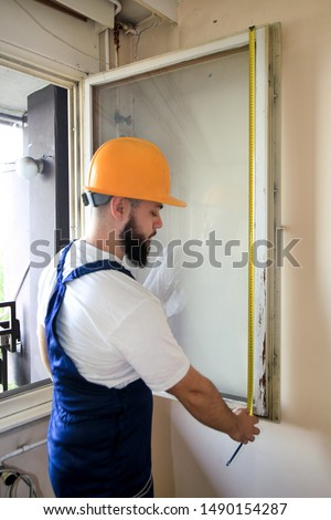Construction worker and handyman is working on renovation of apartment. Builder is measuring window using measure tape at construction site. House renovation concept. Construction and service tools, blur