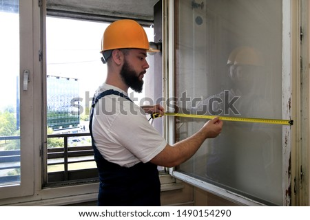 Construction worker and handyman is working on renovation of apartment. Builder is measuring window using measure tape at construction site. House renovation concept. Construction and service tools.