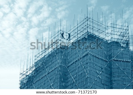 construction worker assembling scaffold on building site with sky background