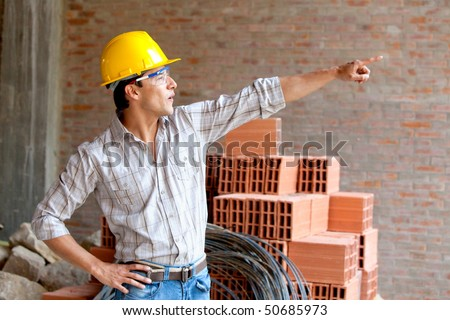 Construction worker at a building site pointing at something
